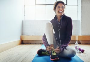 Shot of an attractive young woman tying her shoelaces while working out at home