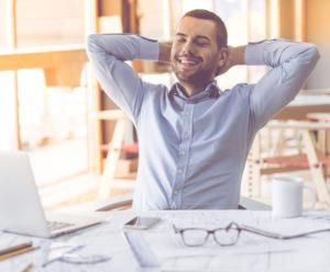 entspannter Mann am Schreibtisch bei der Arbeit