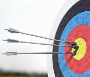 drei Pfeile stecken in der Mitte einer Zielscheibe