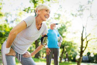 Zwei Senioren treiben im Wald Sport. Die Frau lächelt