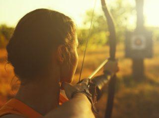 Frau mit Pfeil und Bogen zielt auf Zielscheibe